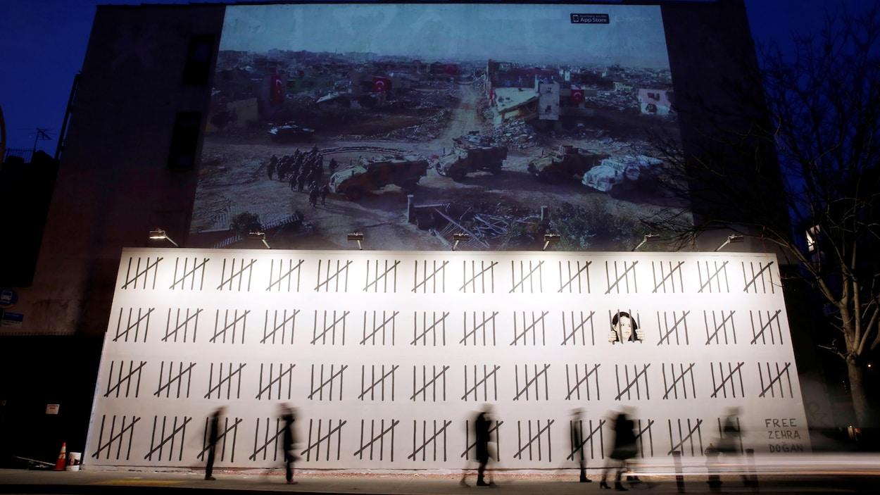 Des passants flous marchent devant la murale géante de Banksy, à New York. Sur ce mur blanc, des traits noirs représentent les jours passés en prison par la journaliste. On voit aussi son visage derrière quatre traits qui prennent l'aspect d'une prison.