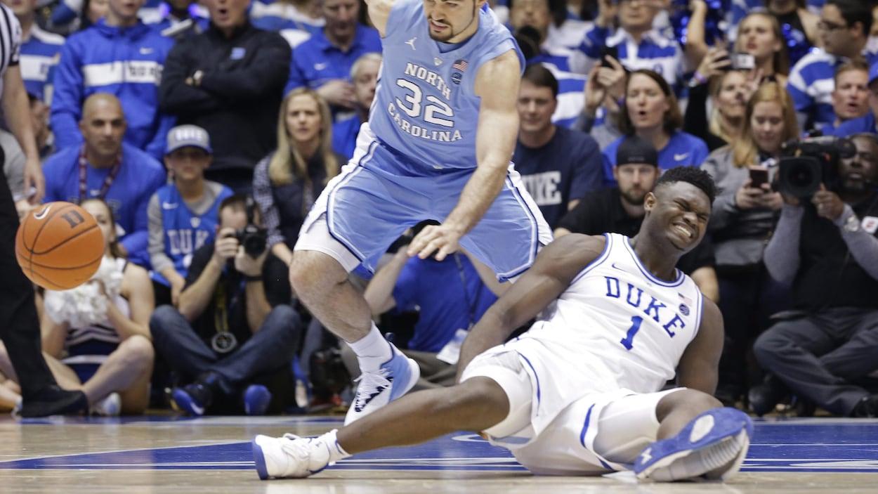 Un joueur de basketball assis au sol grimace de douleur, son soulier de sport visiblement fendu du talon aux orteils.
