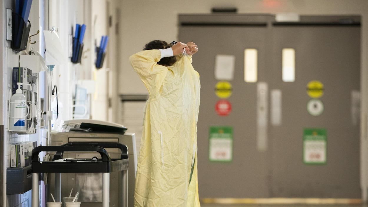 Une femme noue une blouse médicale.