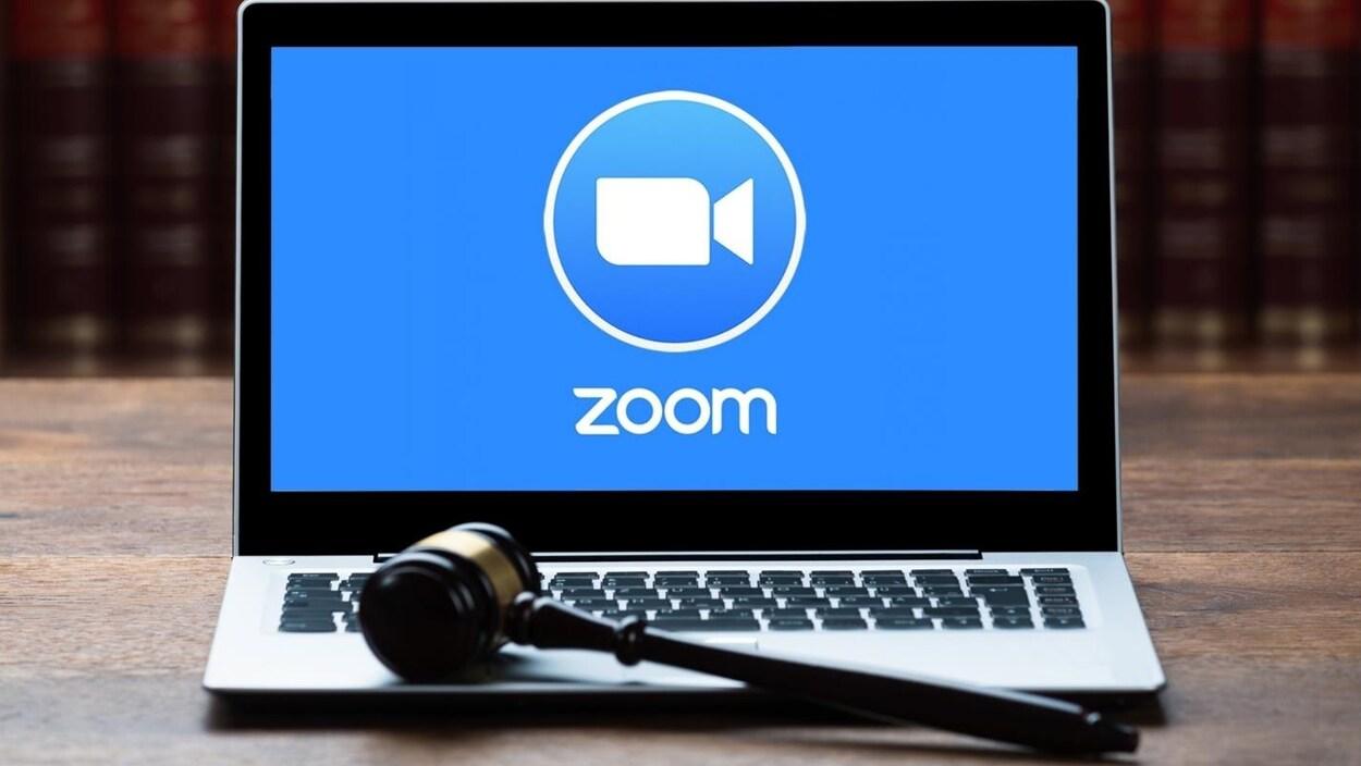 Un marteau de juge placé devant un ordinateur qui affiche le logo de Zoom.