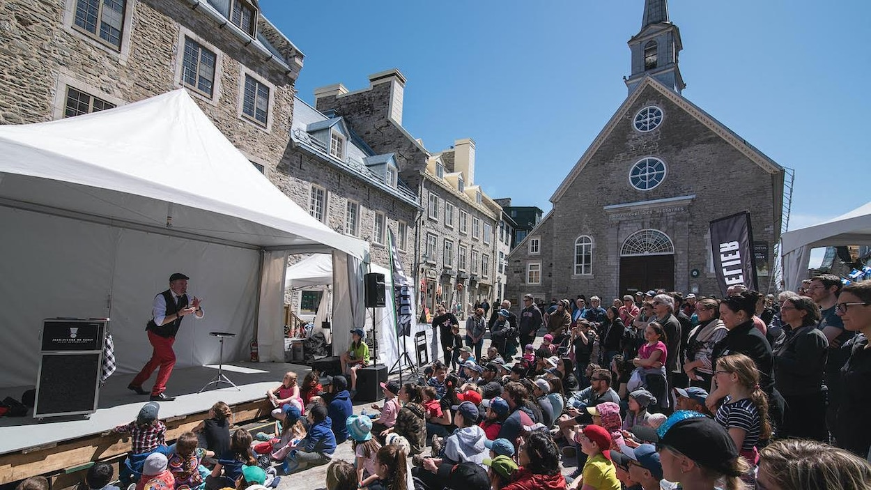 Magicien sur scène offrant un spectacle extérieur à la Place Royale à Québec lors d'une journée ensoleillée