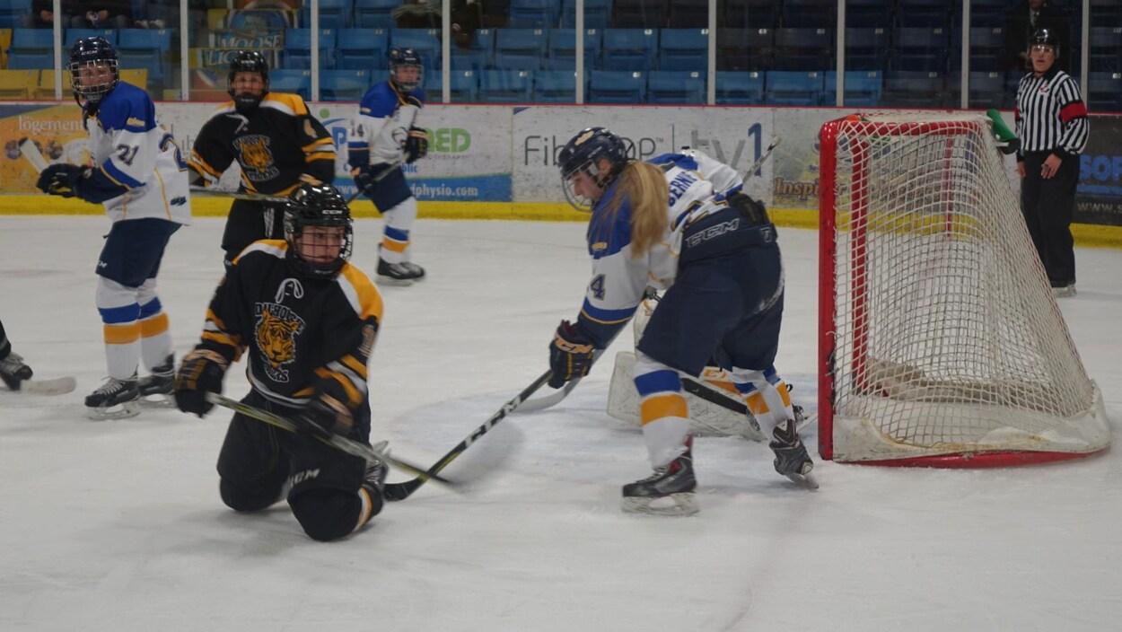 Des joueuses devant un filet de hockey.