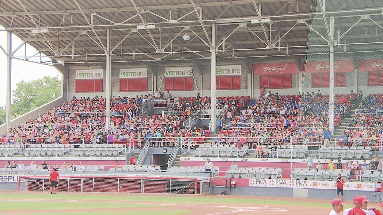 Les centaines d'élèves sont assis dans les gradins et regardent le match qui s'apprête à commencer.
