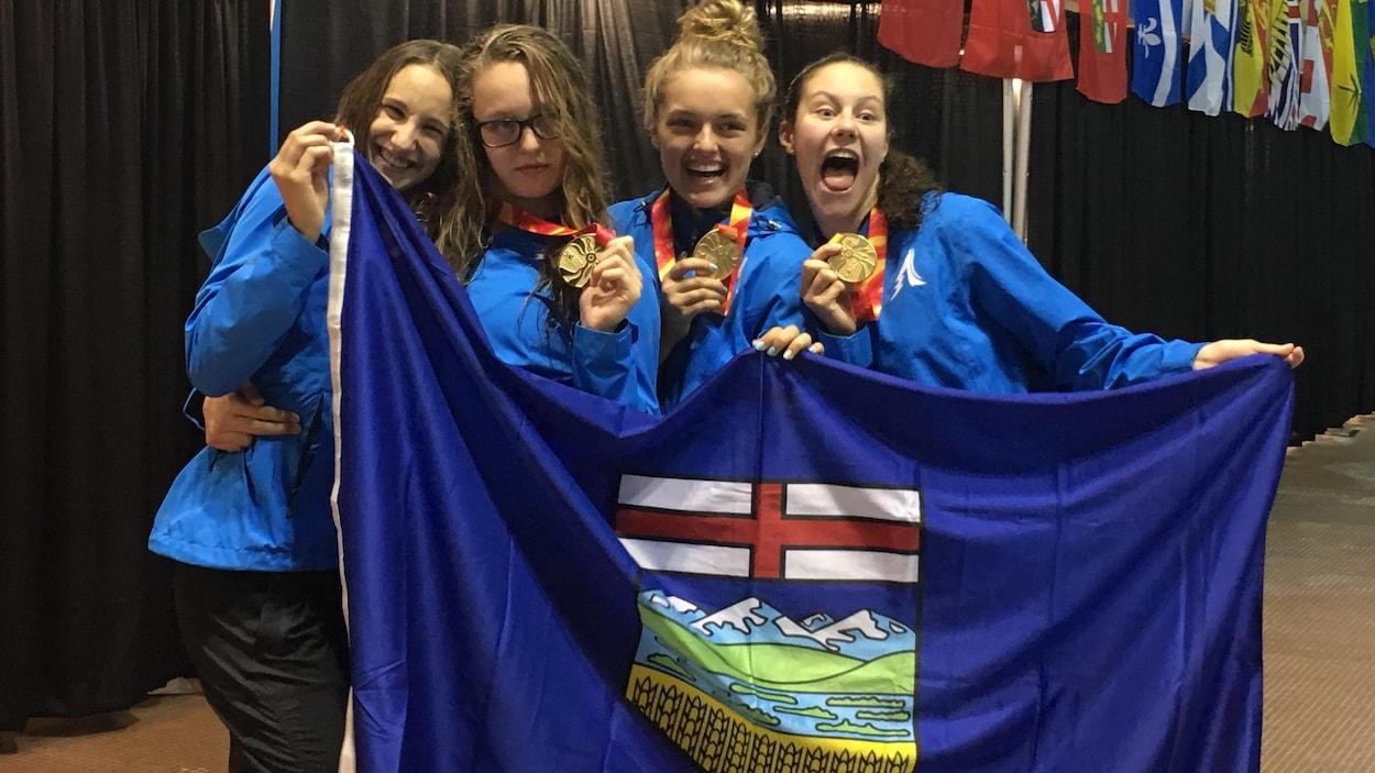 Maria Olarescu, Avery Wiseman, Kyla Nelson et Alexandra Butler montrent fièrement la médaille d'or qu'elles ont remporté au relais quatre fois 50 m quatre nages.