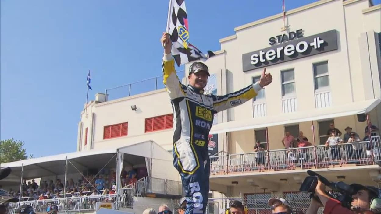 Un pilote de course automobile sourit et tient le drapeau à damiers d'une main sur le toit de son véhicule.