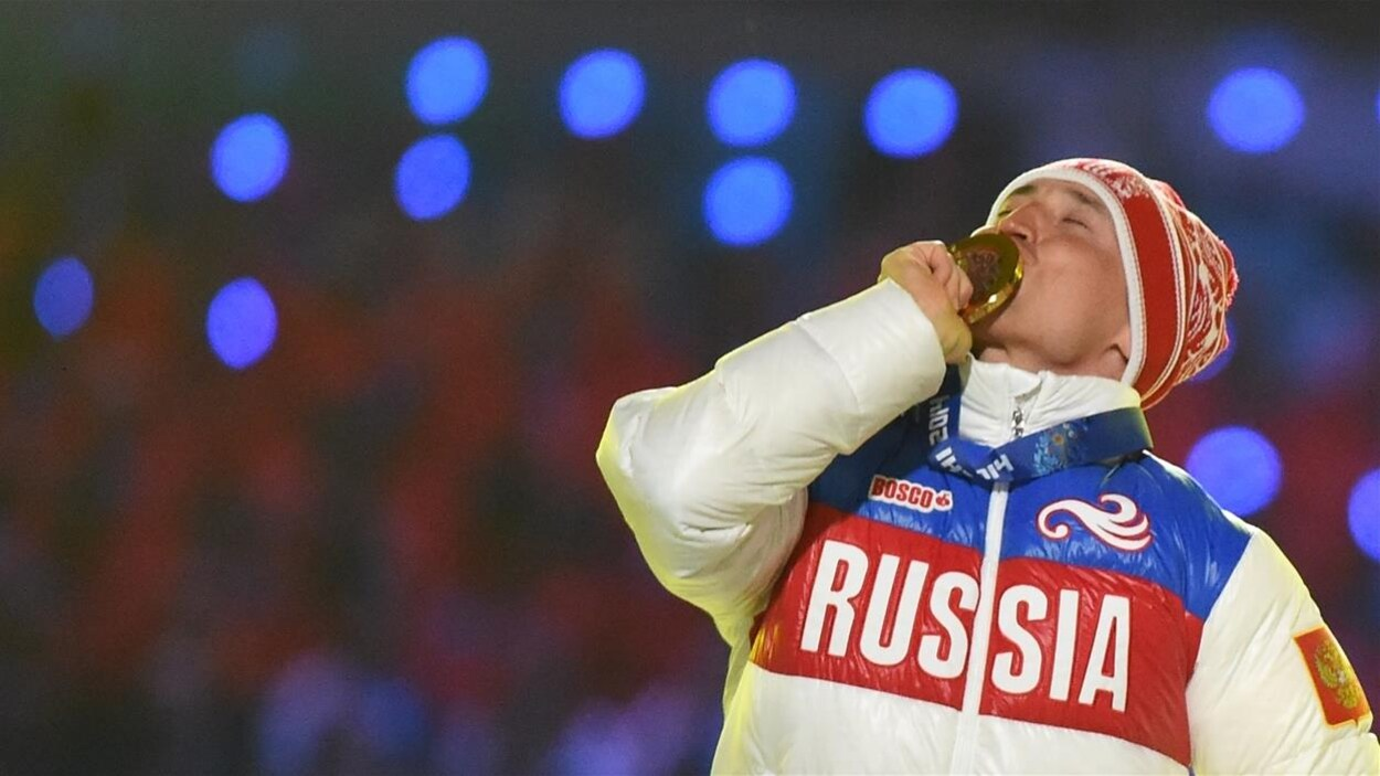 Alexander Legkov embrasse sa médaille d'or sur le podium.