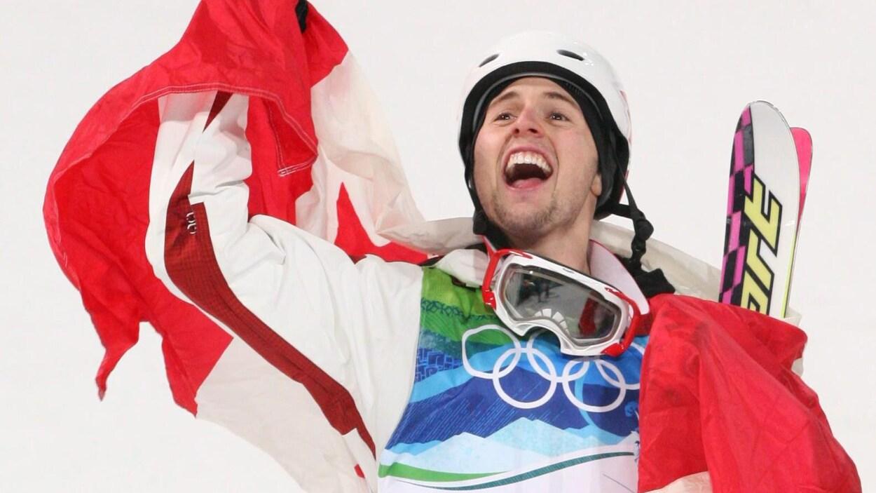 Drapé du drapeau canadien, il lève le bras en l'air.