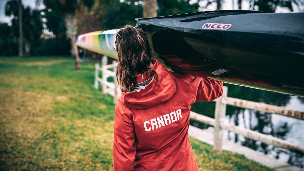 Andréanne Langlois transporte son kayak sur une épaule. On la voit de dos.