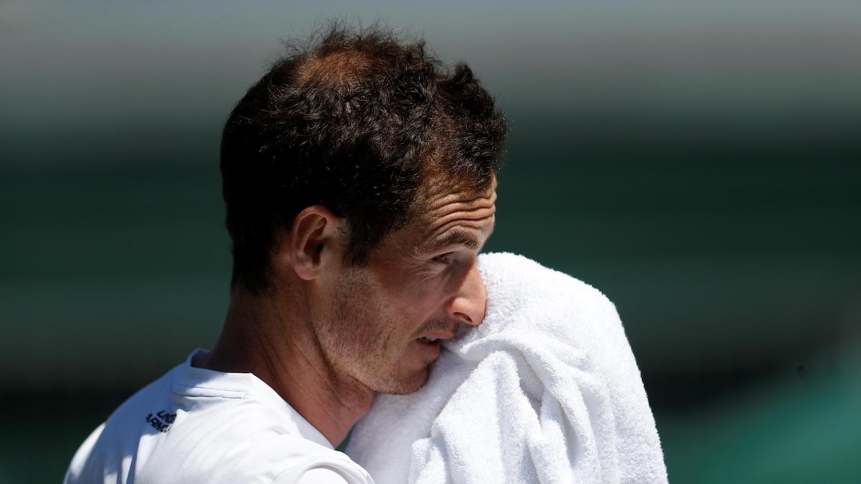 Il s'essuie le visage pendant un entraînement à Wimbledon.