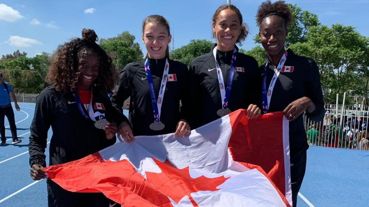 Quatre jeunes femmes posent avec un drapeau du Canada après une course.