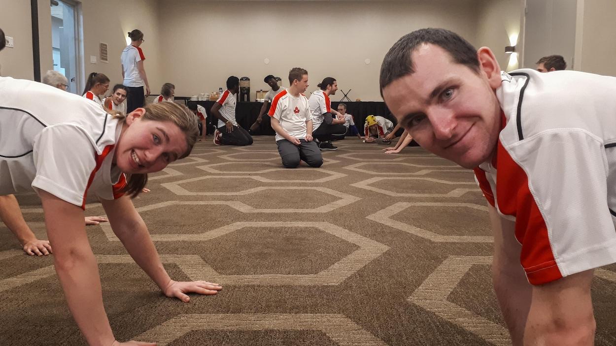 Ils font des étirements dans une salle, les mains au sol, et regardent la caméra.