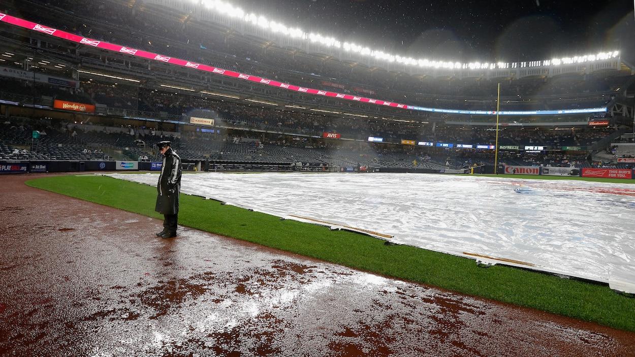 Un policier surveille le terrain du Yankee Stadium pendant une averse en 2018.