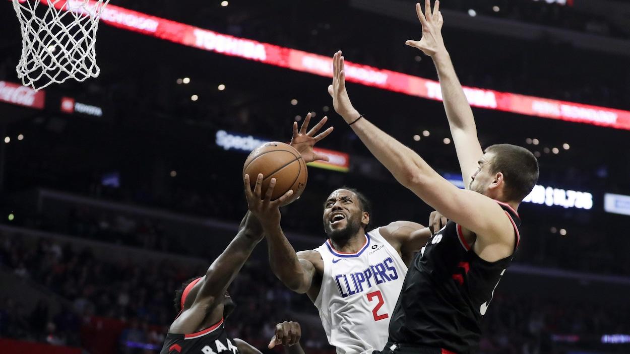 Leonard se faufile entre les deux joueurs des Raptors de Toronto.