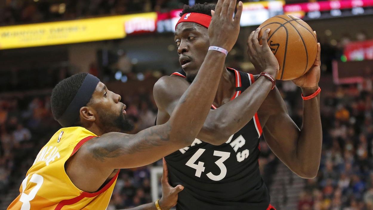 Un homme protège le ballon devant un adversaire lors d'un match de basketball.