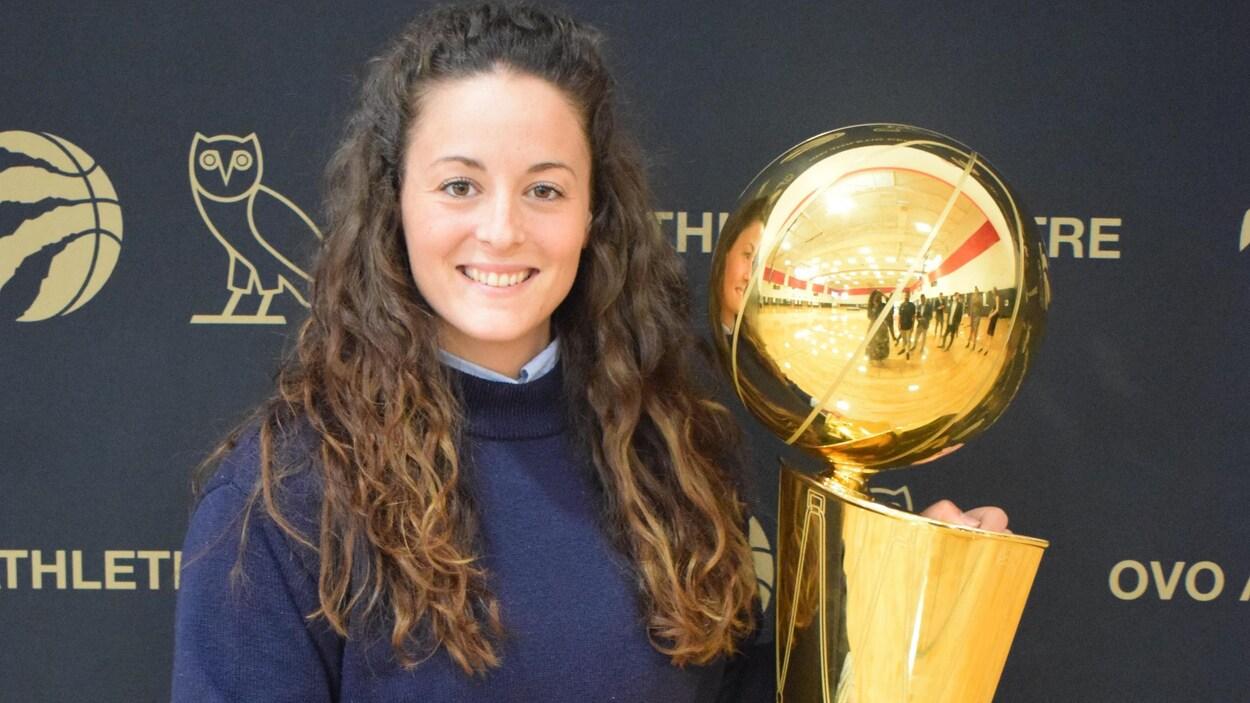 Une jeune entraîneuse de basketball tient le trophée de la NBA devant la caméra.