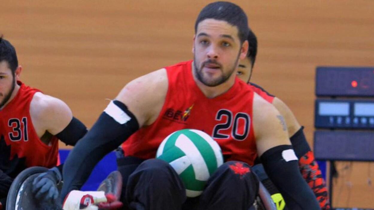 Un joueur en fauteuil roulant transporte un ballon de rugby.
