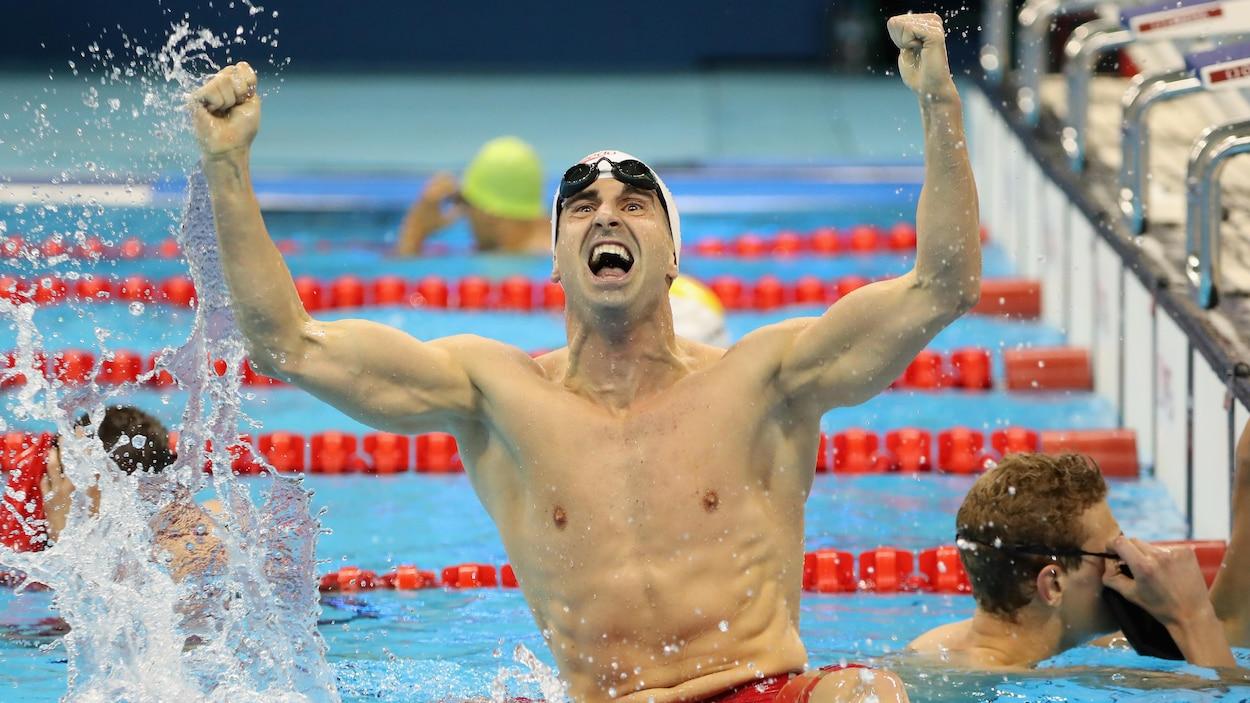 Un nageur lève les bras en triomphe dans son couloir après sa course.