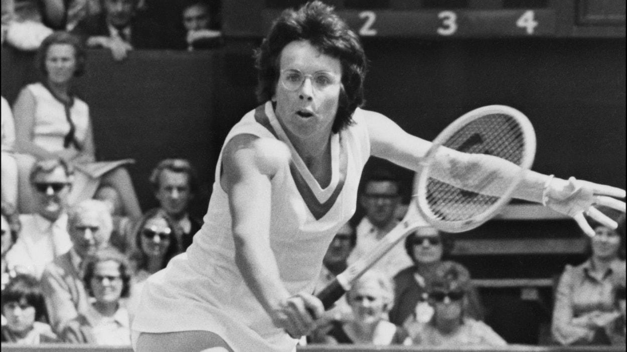 Une photo en noir et blanc d'une joueuse de tennis qui tente de retourner une balle.