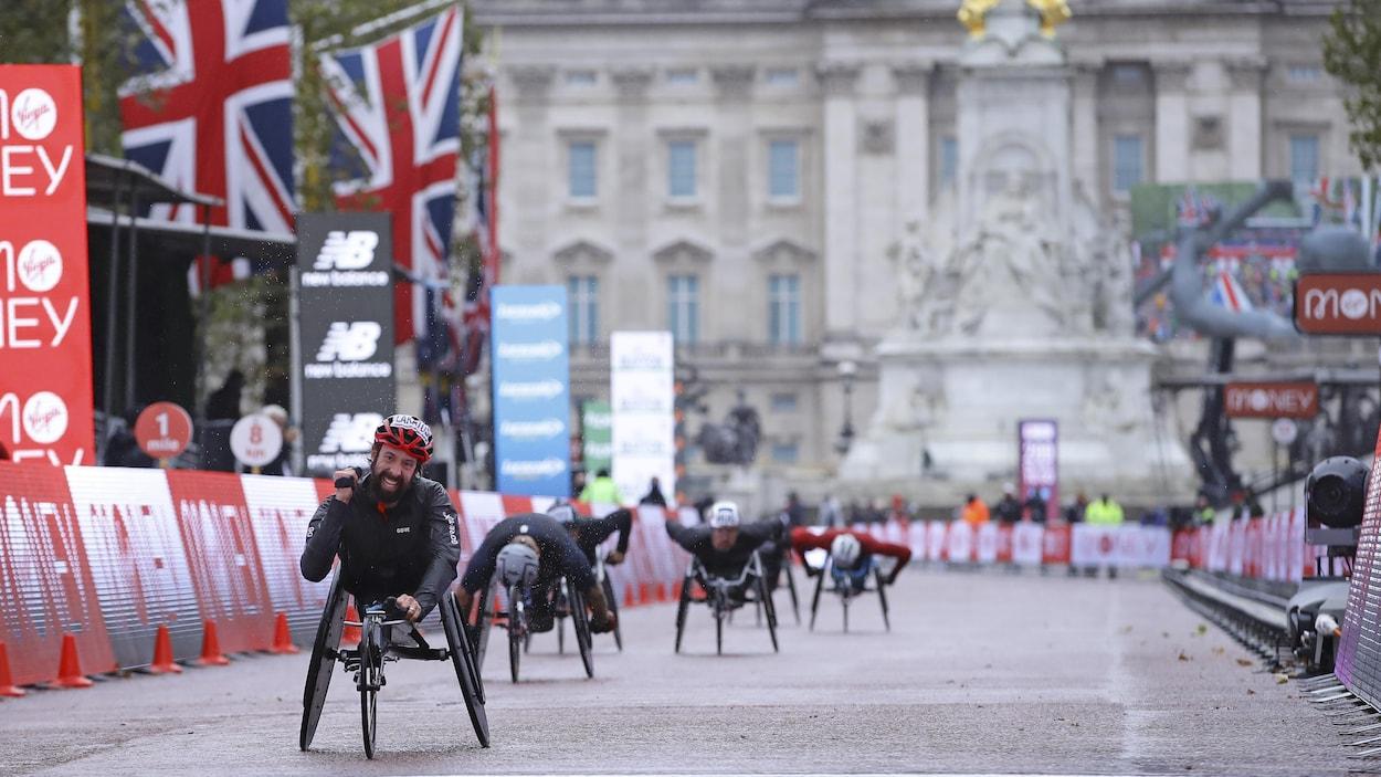 Un athlète en fauteuil roulant, vêtu de noir et d'un casque rouge, franchit le fil d'arrivée au marathon de Londres.