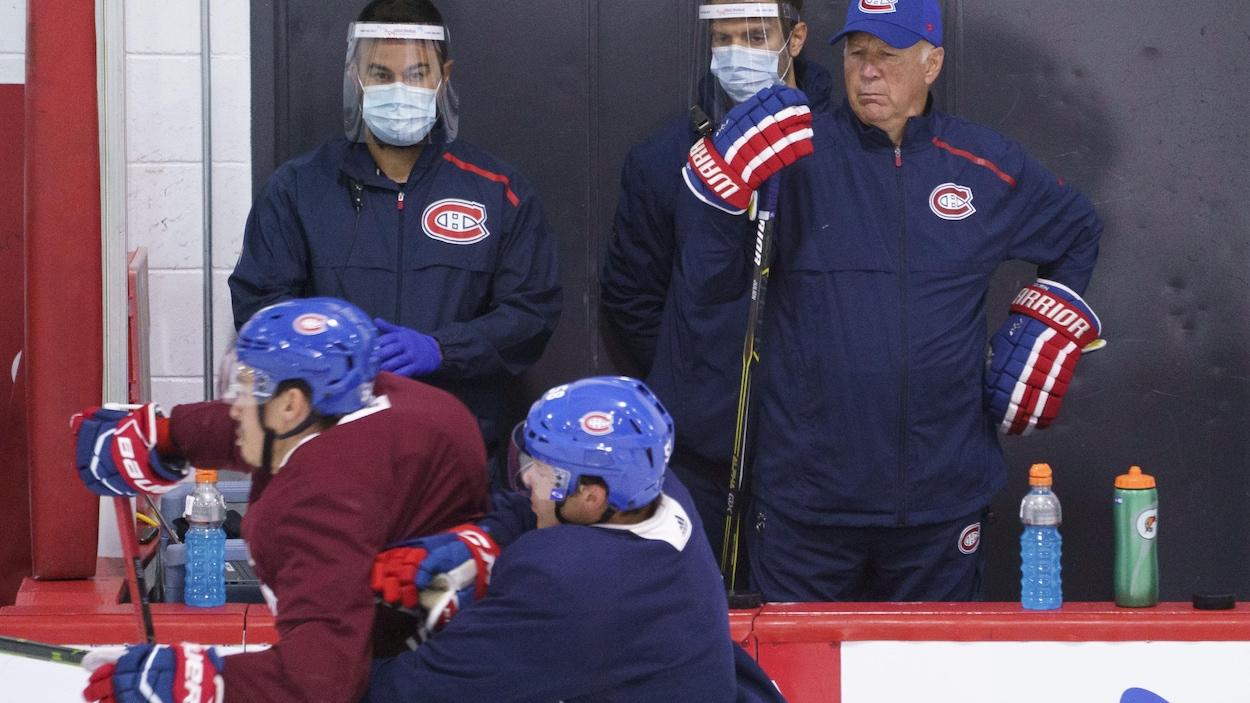 Un entraîneur regarde du banc ses joueurs.