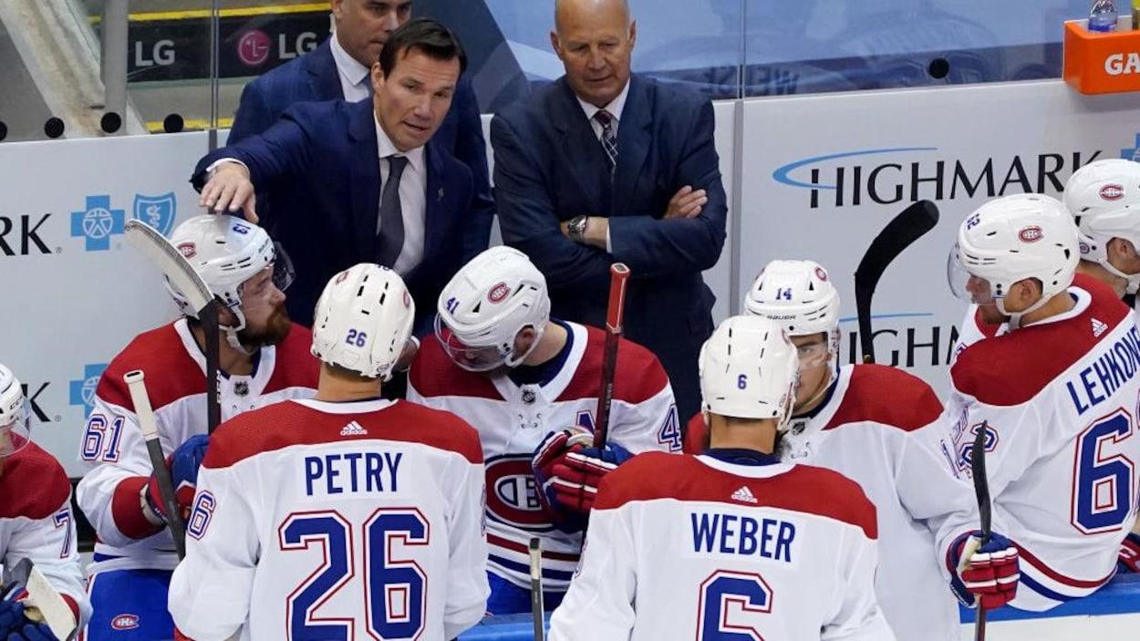 Des joueurs écoutent leurs entraîneurs près du banc.