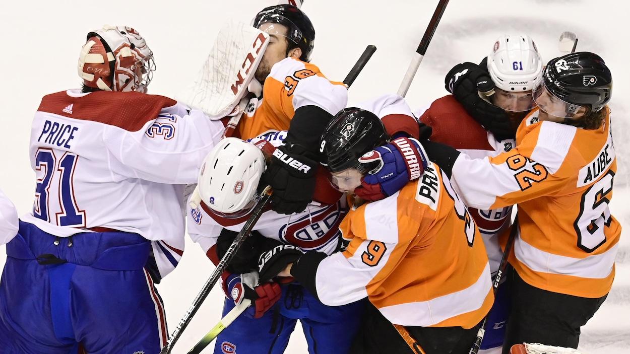Des joueurs de hockey se colletaillent.