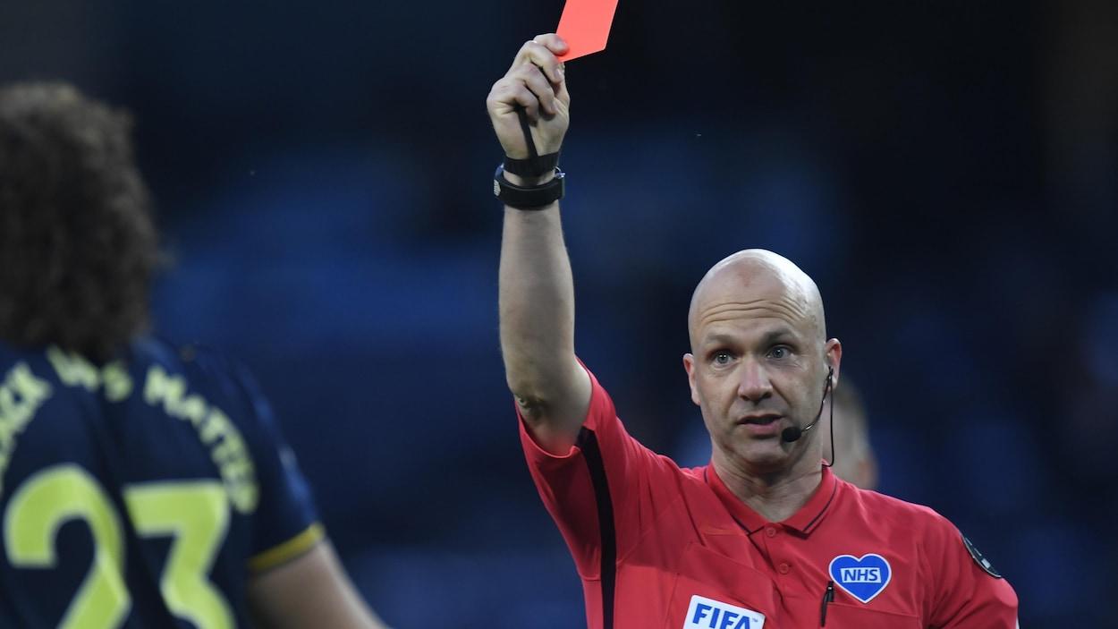 Il lève le carton rouge.