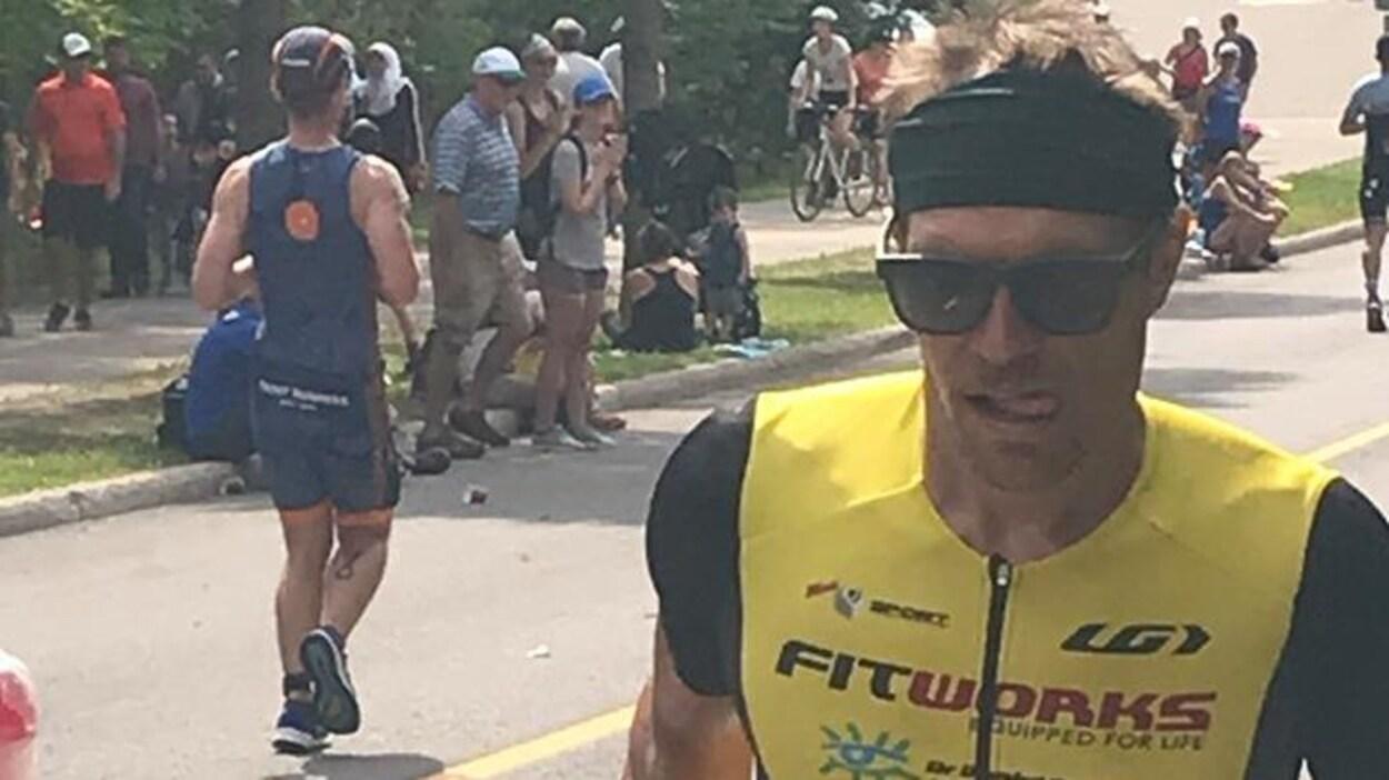 Cédric avec des lunettes fait de la course dans la rue.