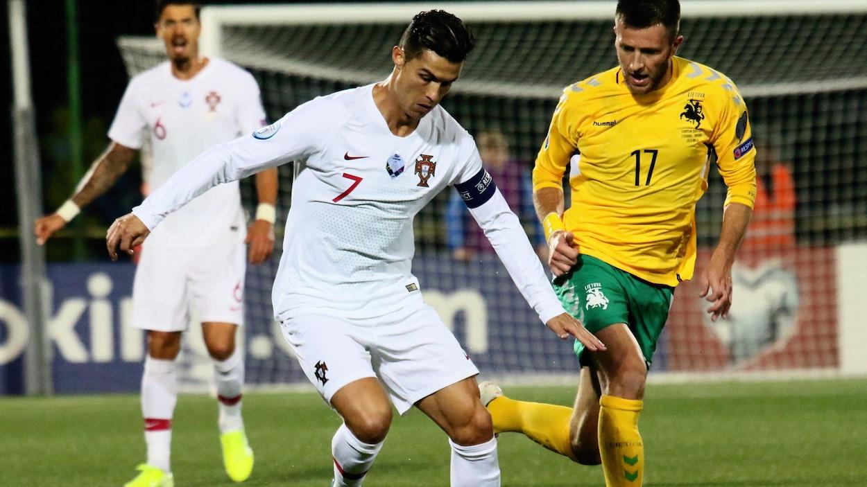 Cristiano Ronaldo, en possession du ballon, bataille avec Mantas Kuklys, de la Lituanie.