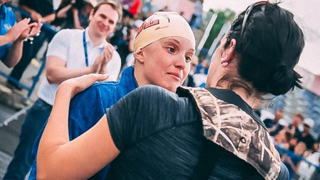 L'entraîneuse tient son athlète par les épaules.