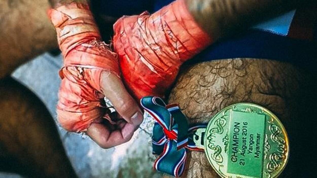 Dave Leduc tient la médaille du champion après son combat contre Tun Tun Min.