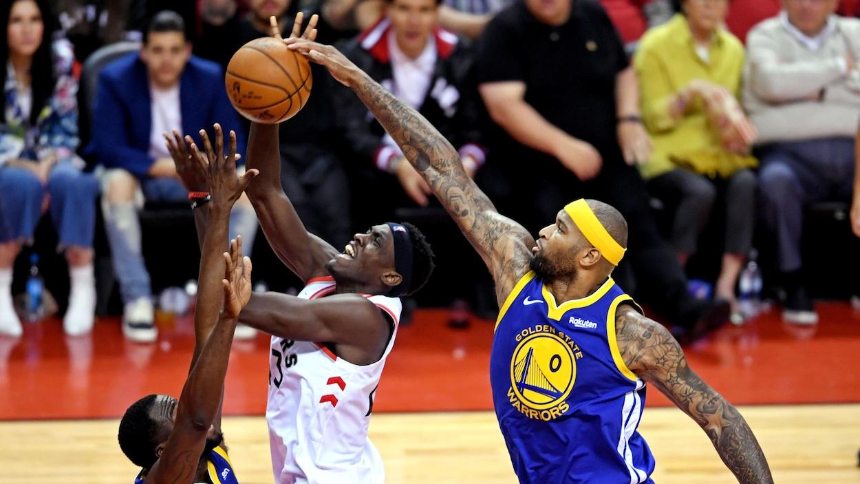 Un joueur tente d'empêcher un adversaire de marquer un panier.