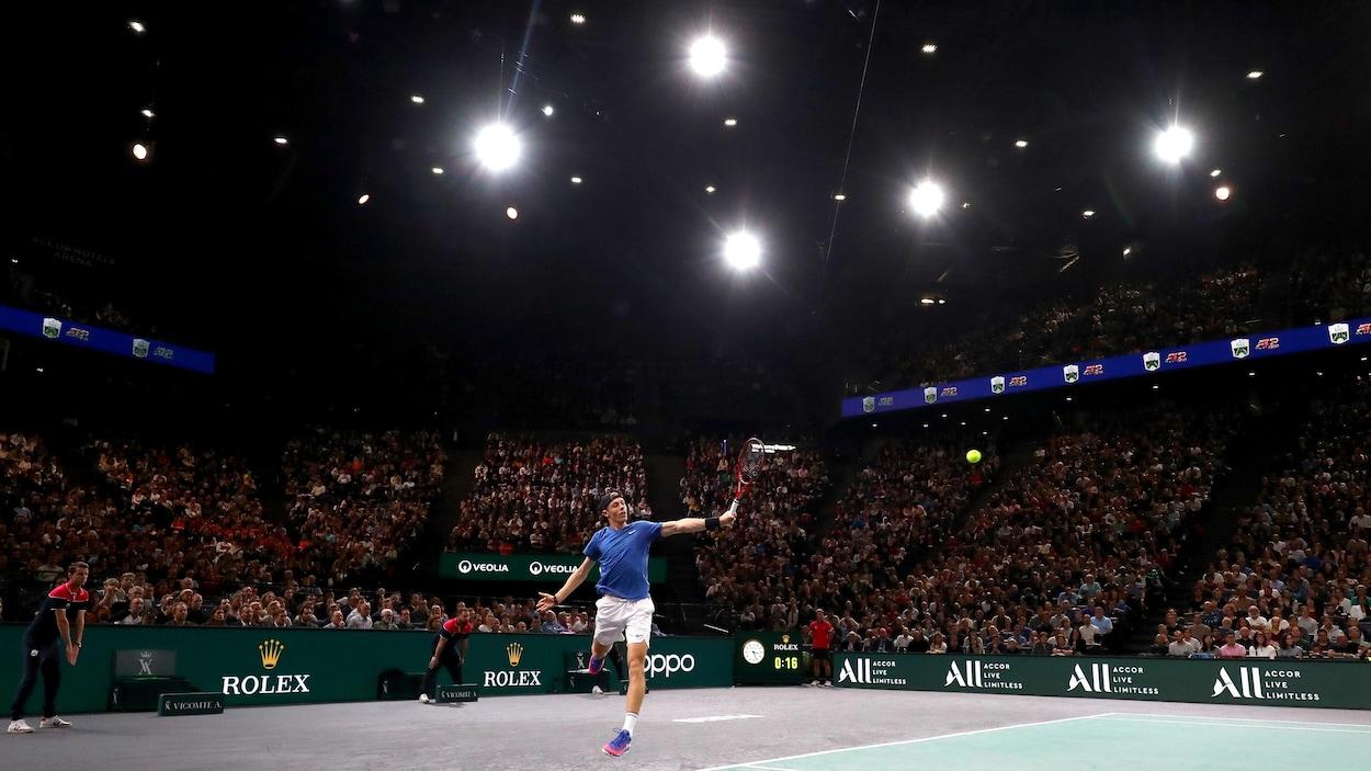 Un joueur de tennis retourne une balle en sautant. Il est devant des gradins bondées.