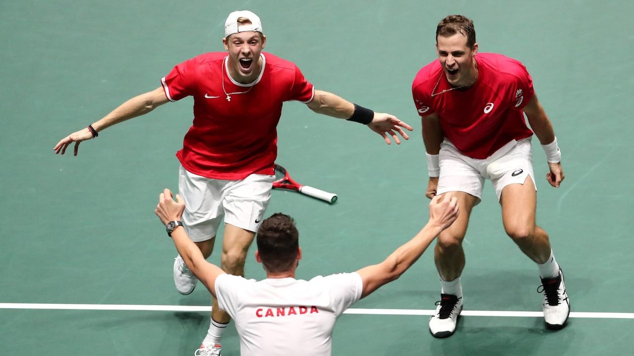 Les joueurs canadiens du double célèbrent leur victoire avec leur entraîneur.