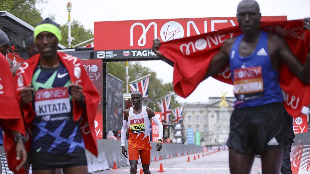 Un coureur vêtu de blanc et rouge franchit le fil d'arrivée pendant que le vainqueur célèbre sa victoire.
