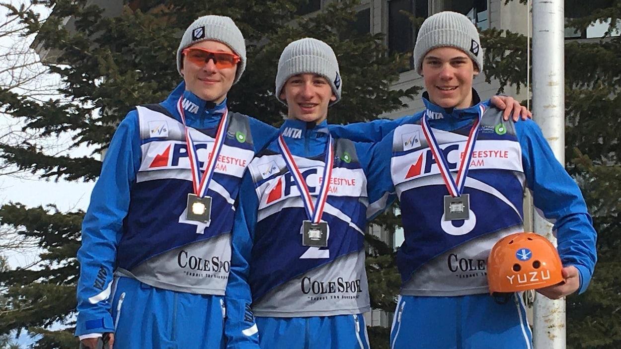 Trois athlètes sur un podium.
