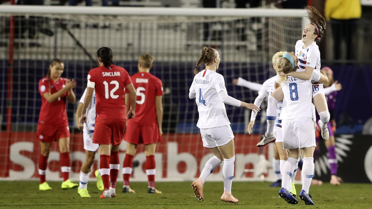Rose Lavelle saute dans les bras de ses coéquipières américaines après avoir marqué le premier but du match contre les Canadiennes.