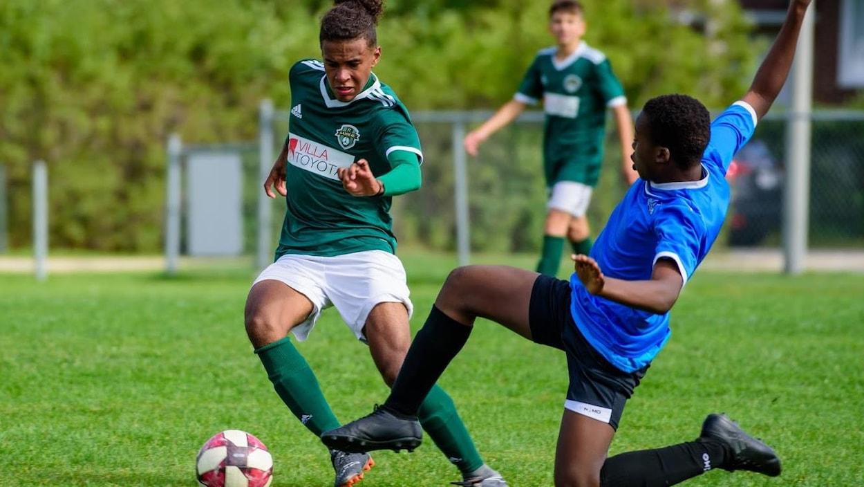 Un joueur de soccer tente un tacle sur un adversaire.