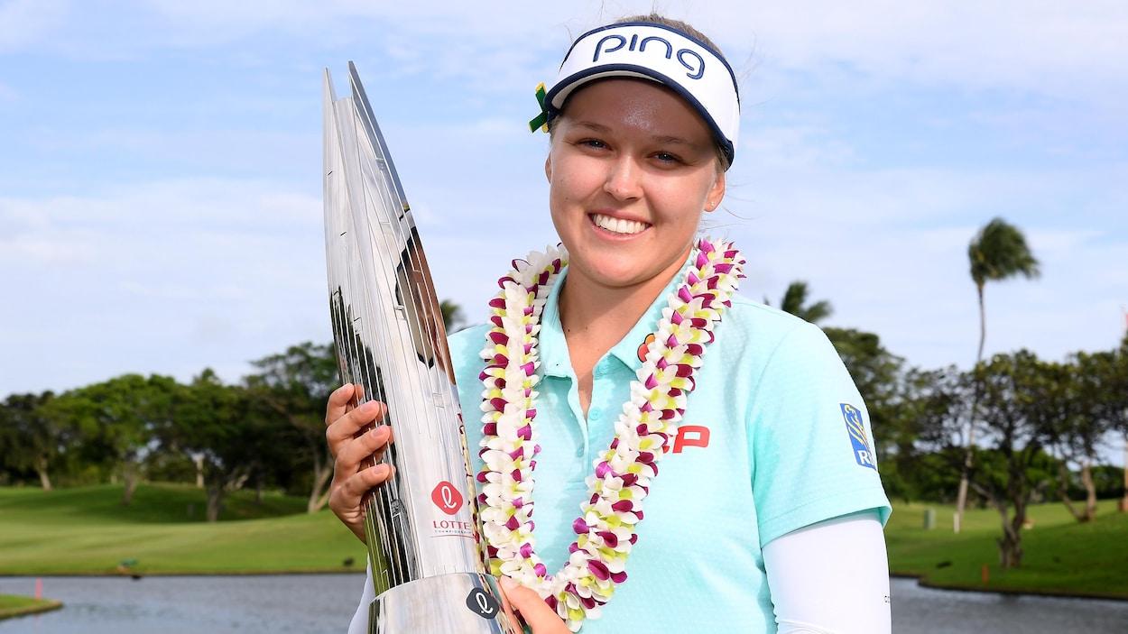 Brooke Henderson soulève son trophée de gagnante du Championnat Lotte.