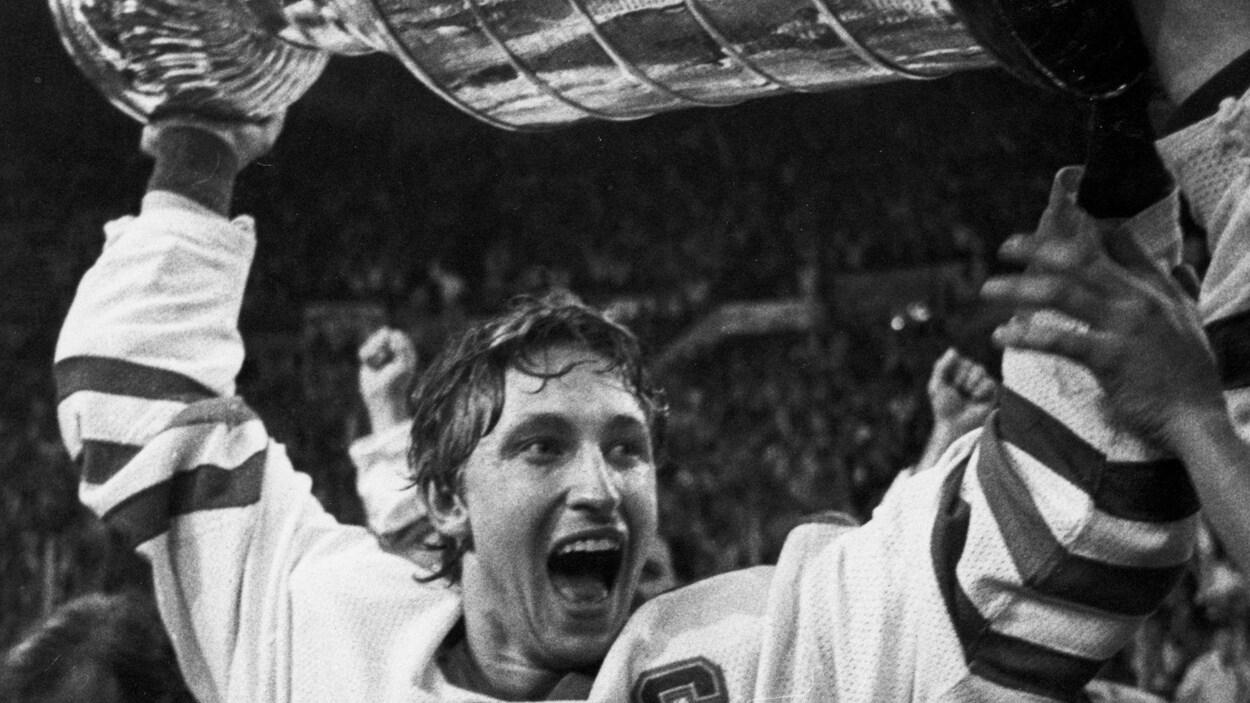 Photo en noir et blanc où on voit Wayne Gretzky soulever la Coupe Stanley