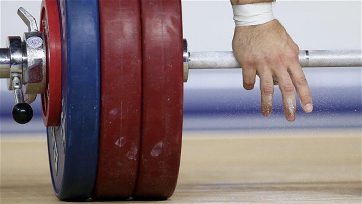 Gros plan des mains d'un haltérophile qui s'apprête à soulever une charge.