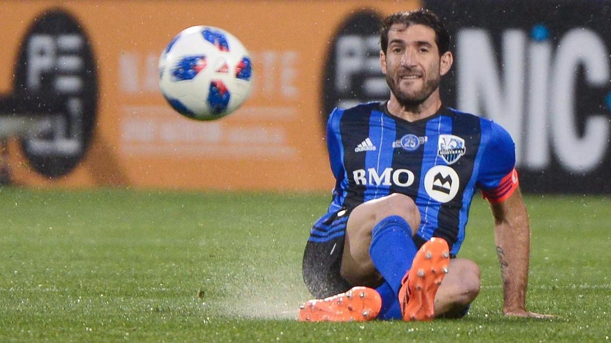 Il est assis sur le terrain et regarde le ballon devant lui.
