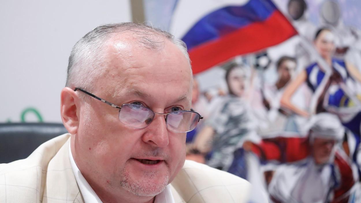 Un homme en point de presse avec derrière lui un drapeau russe