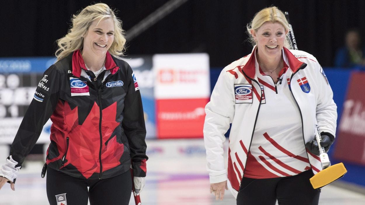 Les capitaines canadienne et danoise, Jennifer Jones et Angelina Jensen, rient en marchant côte-à-côte sur la patinoire.