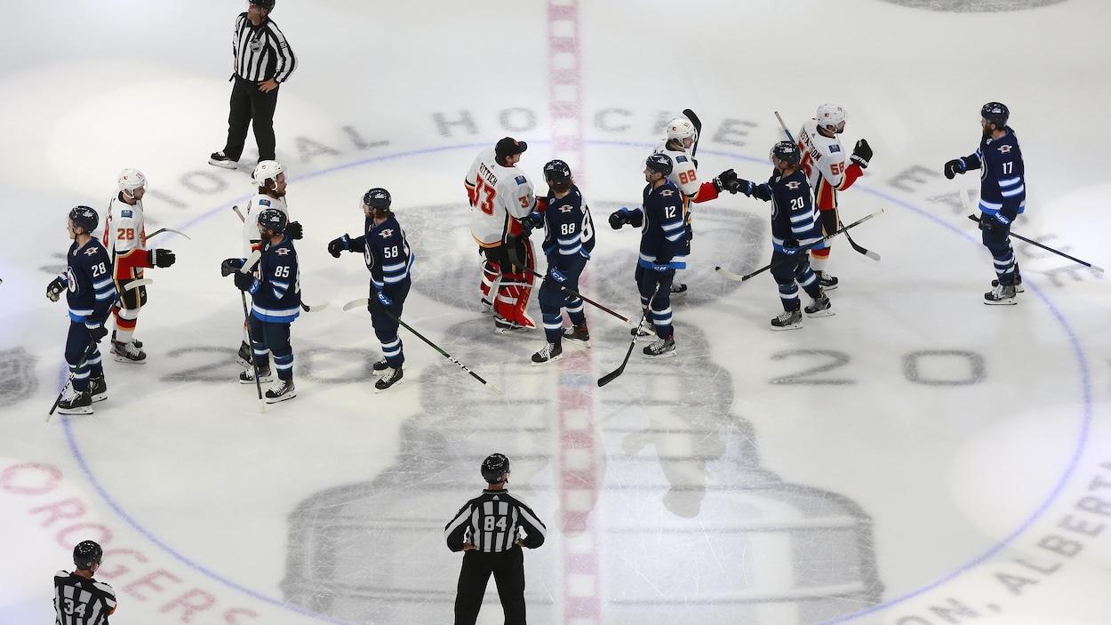 Les joueurs des Jets et des Flames se donnent la main à la suite de l'élimination des Jets.