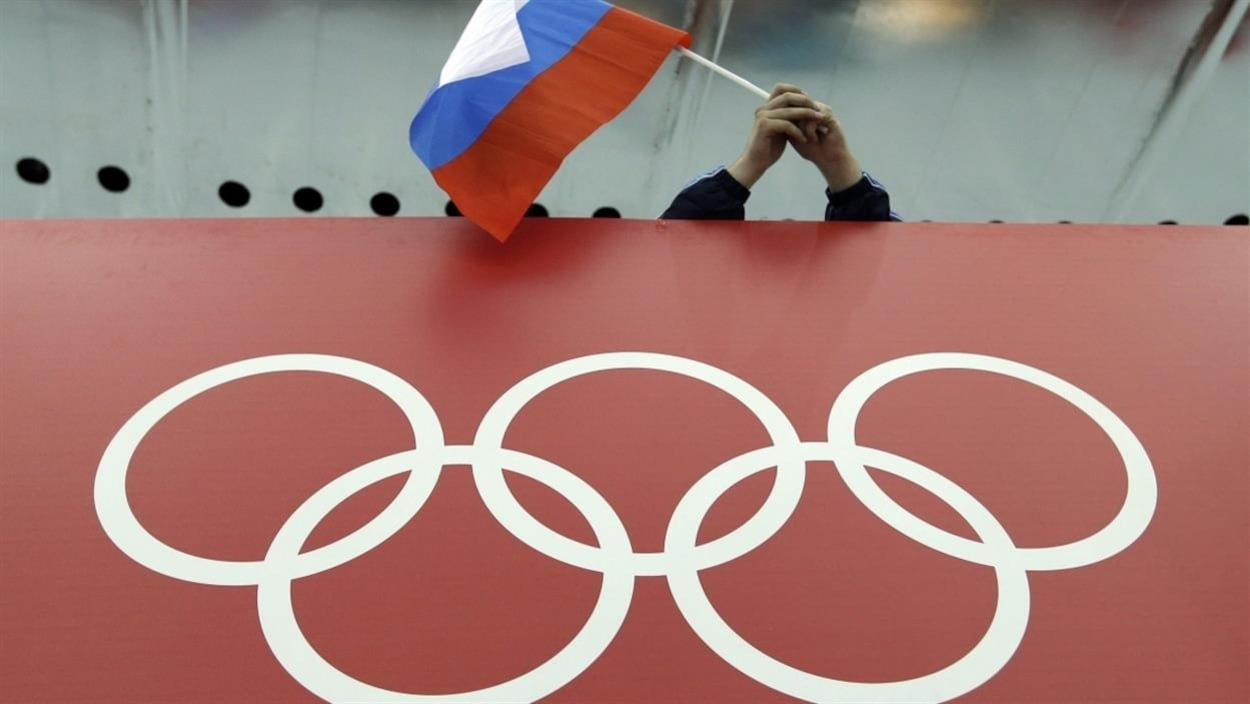 Un drapeau russe tenu au-dessus des anneaux olympiques.
