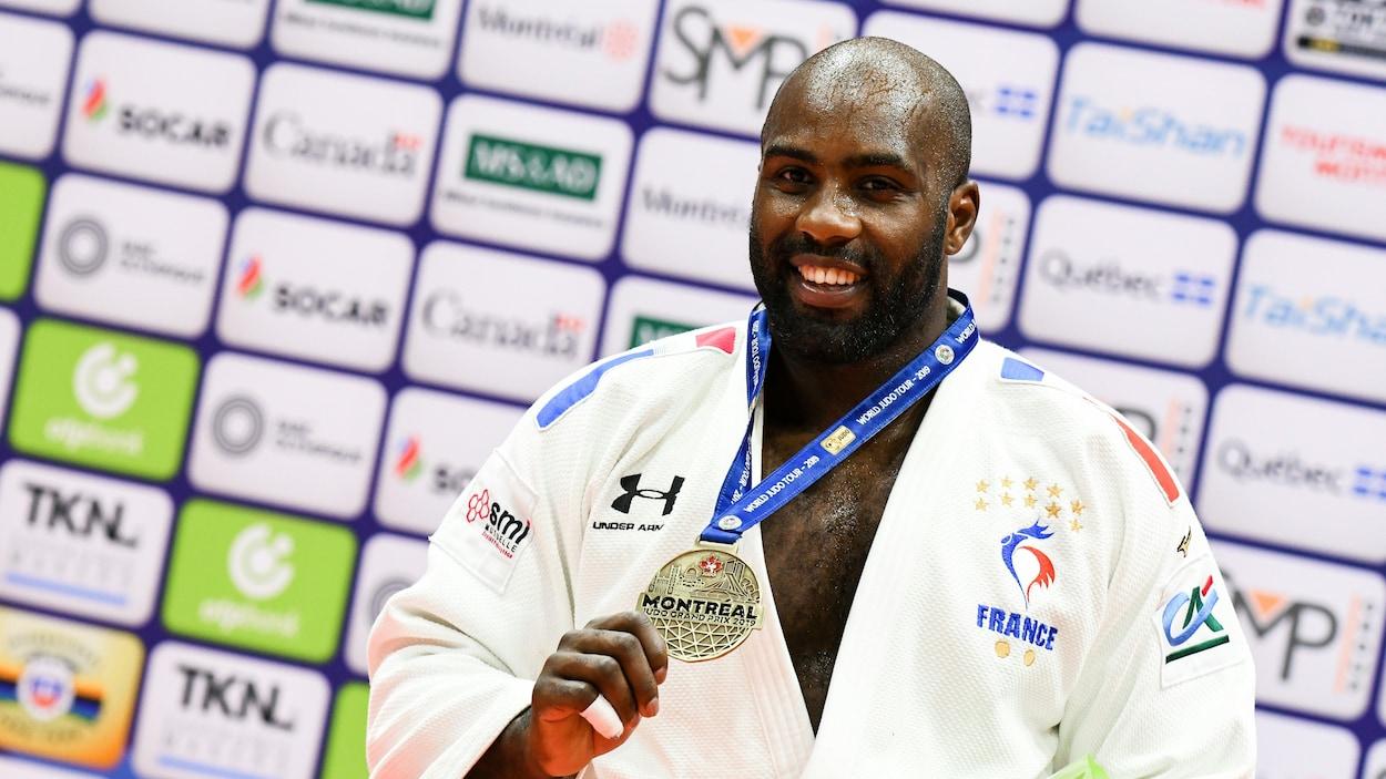 Le judoka français montre sa médaille d'or.