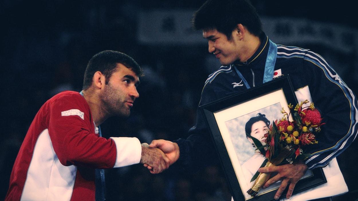 Nicolas Gill et Kosei Inoue se serrent la main sur le podium des Jeux olympiques de Sydney.