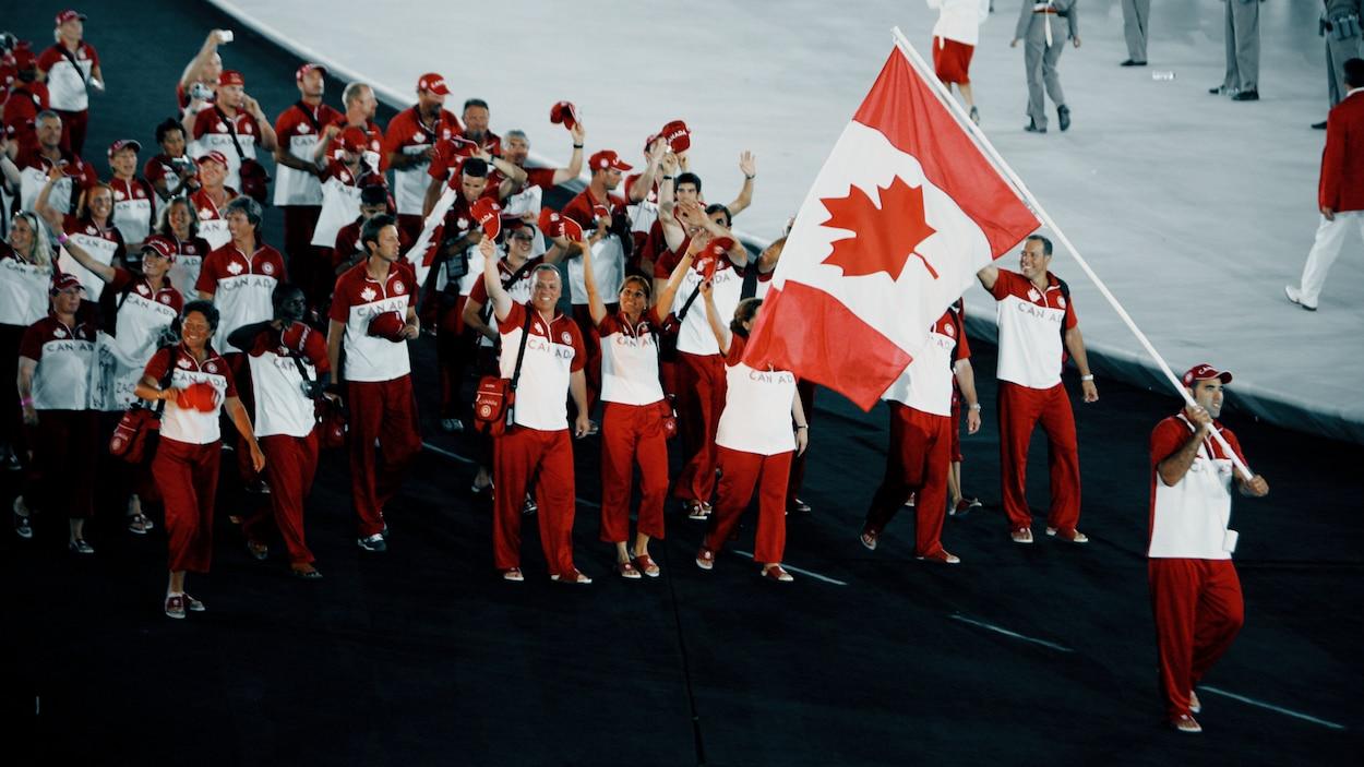 Nicolas Gill agite le drapeau du Canada pendant que le reste de la délégation canadienne le suit.