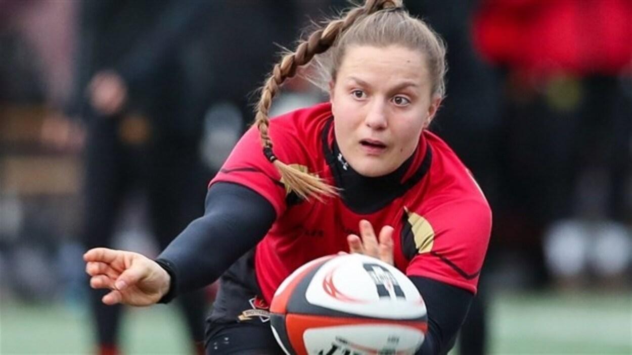 Une joueuse lance un ballon de rugby